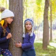 Autumn sister kid girls playing in forest trunk outdoor - Stock Photo