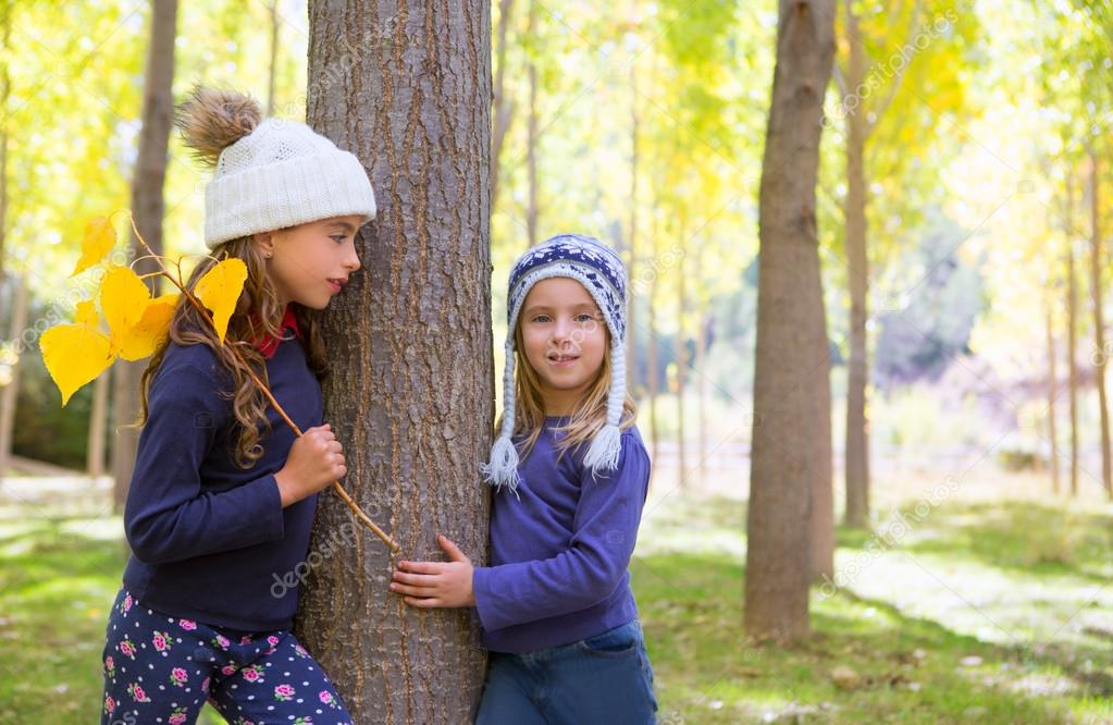 Autumn sister kid girls playing in poplar tree forest near trunk in nature outdoor — Stock Photo #19740157