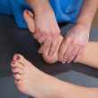 Постер, плакат: Ankle joint mobilization therapy of doctor man to woman