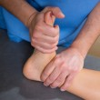 Постер, плакат: Ankle physiotherapy treatment with therapist hands