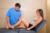 Knee examination doctor to woman patient — Stock Photo