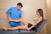 Examination and mobilization of knee joint doctor to woman — Стоковое фото