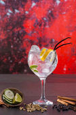 Gin tonic cocktail with spices in red grunge background — Stock Photo