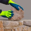 Mason hands working on masonry stone wall - Stock Photo