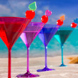 Colorful cocktail in a row with cherry on tropical sand beach — Stock Photo