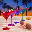 Colorful cocktail in a row cherry on sand palm trees — Stock Photo