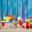 Colorful tropical cocktails at beach on blue wood wall — Stock Photo