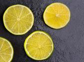 Frescas rebanadas de lima con gotas de agua en negro — Foto de Stock