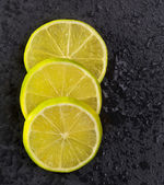 Fresh lima slices with water drops on black — Stock Photo