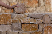 Mason hands working on masonry stone wall — Stock Photo