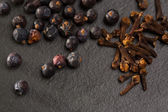 Cloves and juniper berries spices on black slate stone — Stock Photo