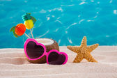 Coconut cocktail on tropical sand beach heart sunglasses — Stock Photo