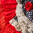 Stock Photo: Flamenco dresses in red blue with spot and red rose
