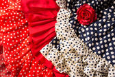 Flamenco dresses in red blue with spot and red rose — Stock Photo