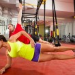 Fitness TRX training exercises at gym woman and man — Stock Photo #25461591