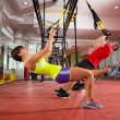 Fitness TRX training exercises at gym woman and man — Stock Photo #25461809