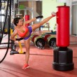 Crossfit woman kick boxing with red punching bag — ストック写真