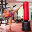 Crossfit woman kick boxing with red punching bag — Stock Photo