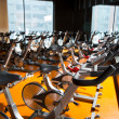 Aerobics spinning exercise bikes gym room in a row - Stock Photo