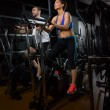 Elliptical walker trainer man and woman at black gym - Photo