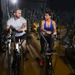 Elliptical walker trainer man and woman at black gym — Foto Stock
