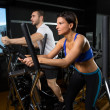 Elliptical walker trainer man and woman at black gym - Foto de Stock
