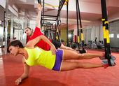 Fitness TRX training exercises at gym woman and man — Stok fotoğraf