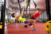 Fitness TRX training exercises at gym woman and man — 图库照片