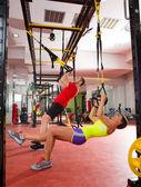 在健身房的女人和男人健身 trx 训练演习 — 图库照片