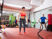 Crossfit gym weight lifting bar woman man battling ropes — Stock Photo