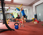 Crossfit woman push ups exercise and man weight lifting — Stock Photo