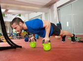 Crossfit fitness man push ups kettlebells pushup motion — Stockfoto