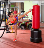 Crossfit woman kick boxing with red punching bag — Photo