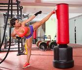 Crossfit žena kick boxu s červeným boxovací pytel — Stock fotografie