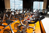 Aerobics spinning exercise bikes gym room in a row — Stock Photo