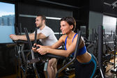 Elliptical walker trainer man and woman at black gym — Stock Photo