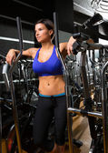 Elliptical walker trainer womman posing relaxed at gym — Stock Photo