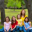 Mother teacher with daughter pupils in playground park — Stock Photo