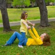 Stock Photo: Daughter and mother playing lying on park lawn