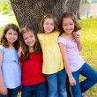 Children group friend girls playing on tree — Stock Photo