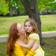 Mother kissing her blond daughter in green park — Stock Photo