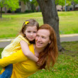Stock Photo: Daughter and mother piggyback smiling in park outdoor