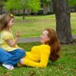Stock Photo: Daughter and mother playing counting lying on lawn
