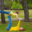 Daughter and mother playing keep balance lying on park — Stock Photo