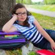Stock Photo: Clever student teen girl with school bag under park tree