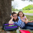 Sister firends girls relaxed under tree park after school — Stockfoto