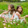 Children friends girls on spring poppy flowers meadow — Stock Photo
