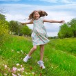 Happy children girl jumping on spring poppy flowers — Stock Photo #26179335