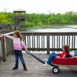 Stock Photo: Girls looking at park lake with outdoor dump cart