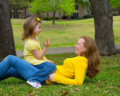 Daughter and mother playing counting lying on lawn — Stock Photo